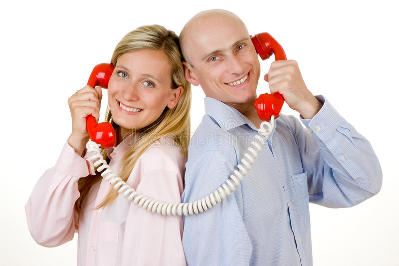 Couple with red telephones. Smiling young couple stood back to back connected with red telephones, isolated on white background royalty free stock image