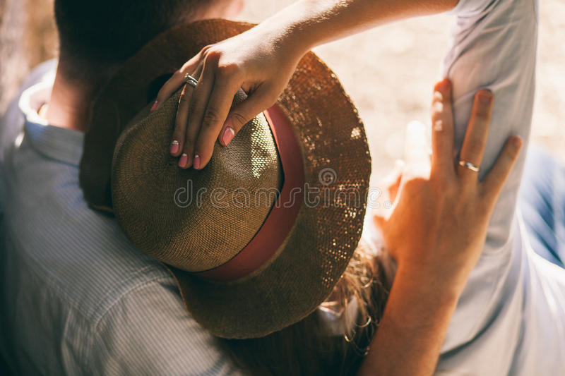 Couple relax and kiss in park. Together. Close up of hands with ring and hat stock image