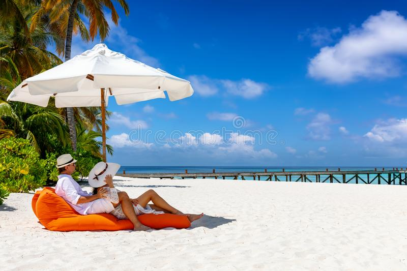 Couple relaxes in a sunbed on a tropical beach in the Maldives stock image