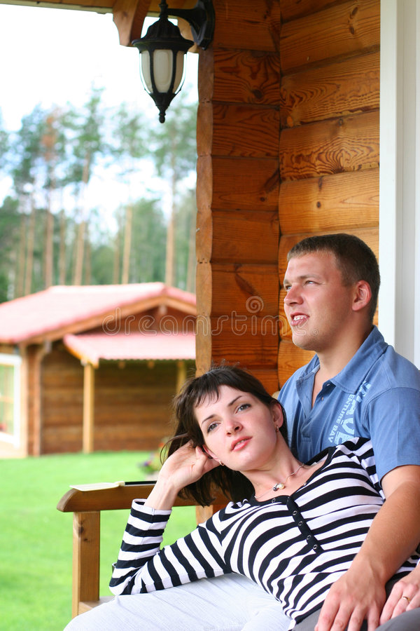 Couple relaxing. Young couple drinking tea on verandah royalty free stock photo