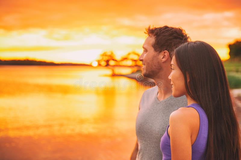 Couple relaxing on beach watching sunset glow over ocean in Caribbean background. Asian girl, Caucasian man interracial stock photography