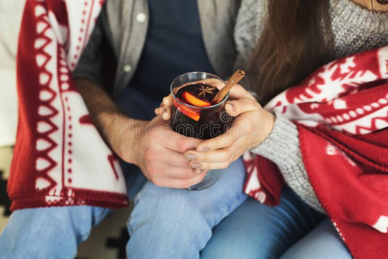 Couple relaxing with glass of warm wine on winter evening royalty free stock image