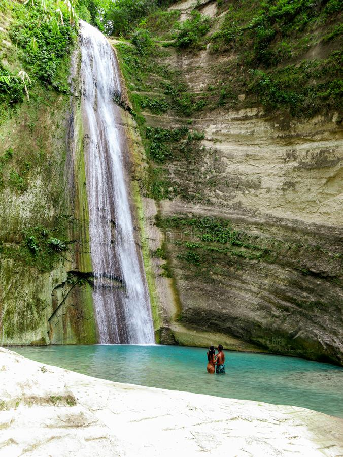 Lovely travel couple at Tropical Waterfall in the jungle in Dao Falls in Cebu Island, Philippines. Couple relaxing on the green canyon road at the middle of stock photo