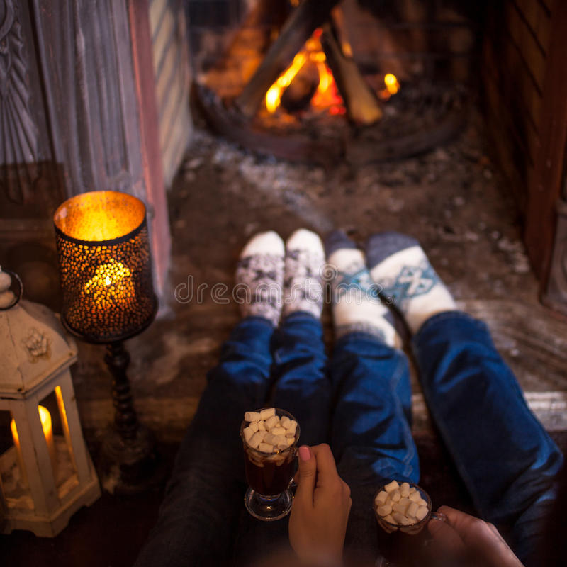 Couple relaxing at home drinking cocoa. Feet in wool socks near fireplace. Winter holiday concept royalty free stock photography