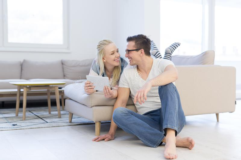 Couple relaxing at home with tablet computers royalty free stock photography