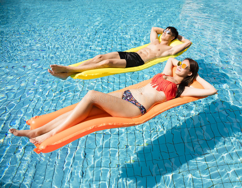 couple relaxing on inflatable raft at swimming pool stock photography