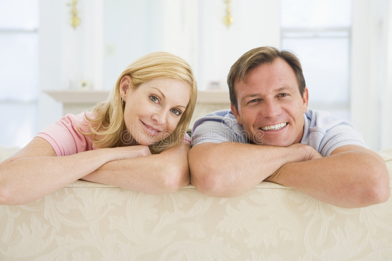 Couple relaxing in living room and smiling royalty free stock photos