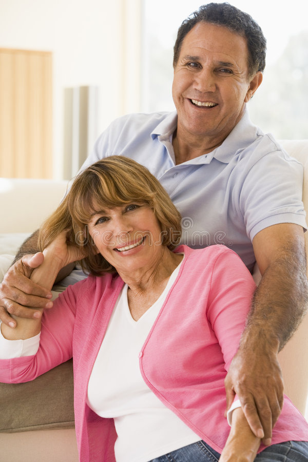 Couple relaxing in living room and smiling stock images