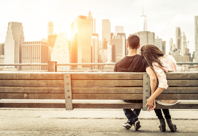Couple relaxing on New york bench in front of the skyline at sun. Set time. concept about love,relationship, and travel