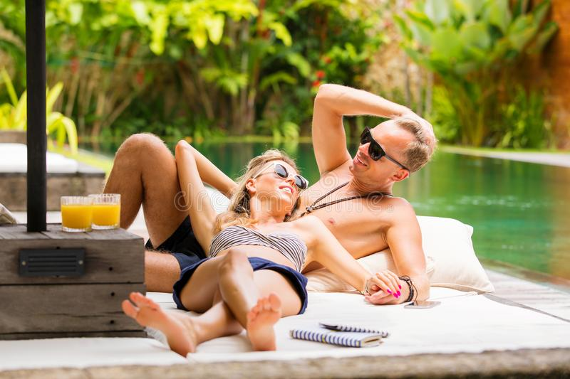 Couple relaxing by the pool stock photos