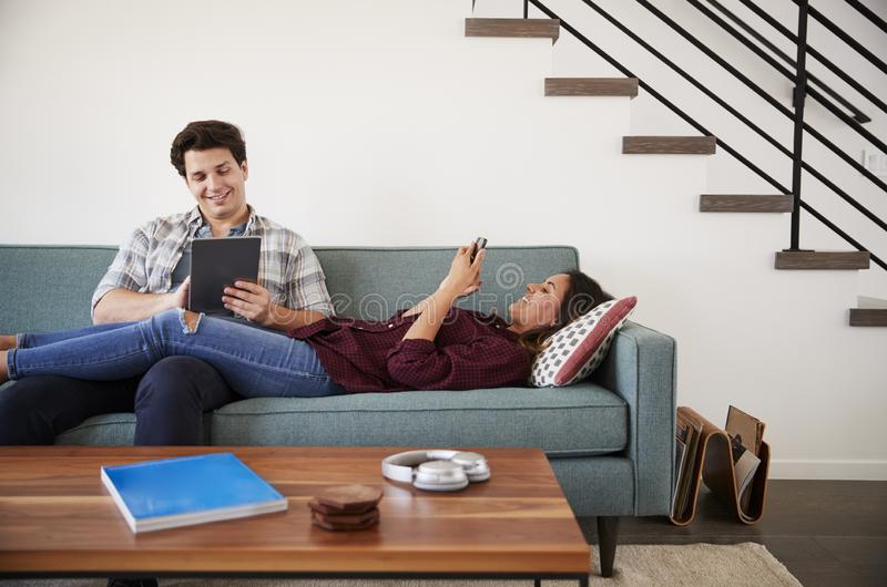 Couple Relaxing On Sofa At Home Using Mobile Phone And Digital Tablet stock image