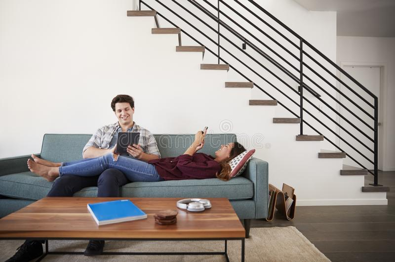 Couple Relaxing On Sofa At Home Using Mobile Phone And Digital Tablet royalty free stock image