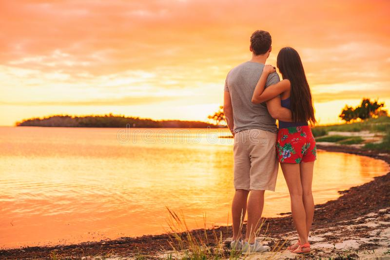 Couple relaxing on summer vacation travel standing on beach watching sunset in tropical destination. Silhouette at dusk from stock image