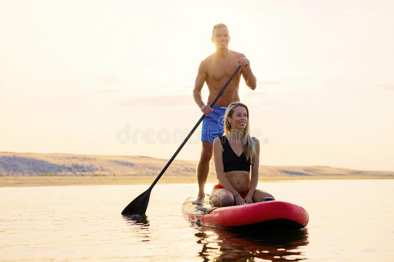 Couple relaxing together on paddle board stock photos