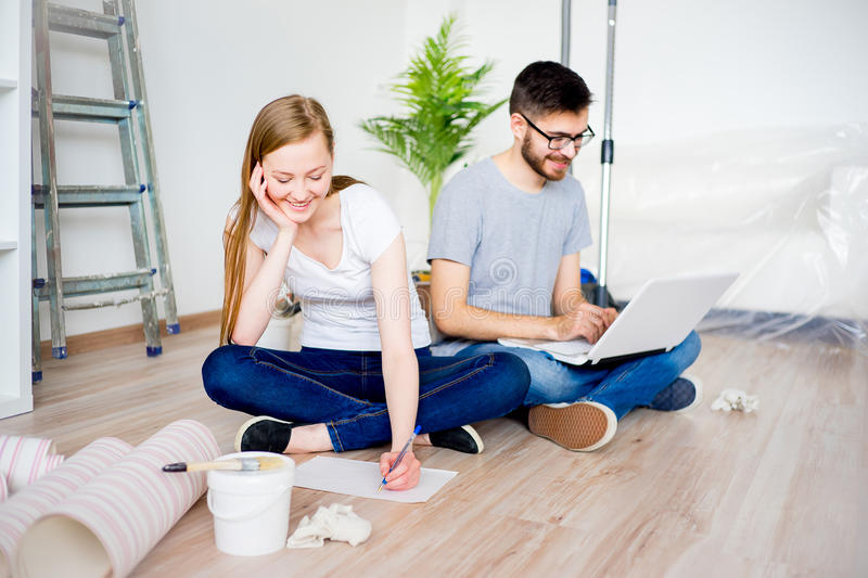Couple renovating apartment. Young couple renovating their new house together royalty free stock image