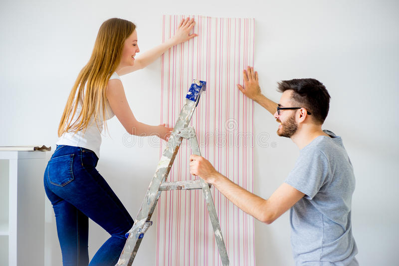 Couple renovating apartment. Young couple renovating their new house together stock photography
