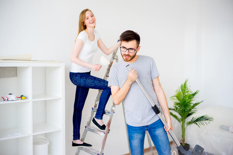 Couple renovating apartment. Young couple renovating their new house together stock image