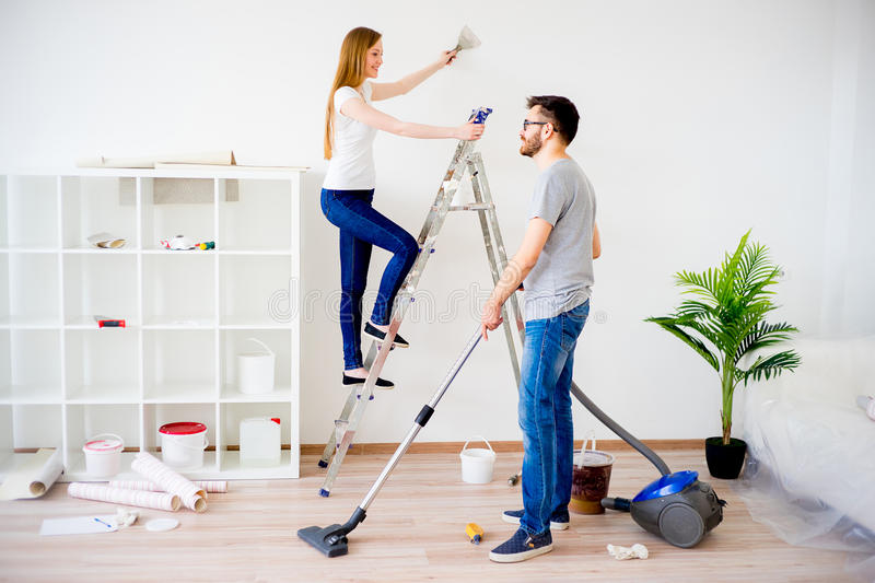 Couple renovating apartment. Young couple renovating their new house together royalty free stock images