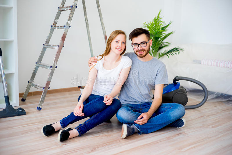 Couple renovating apartment. Young couple renovating their new house together royalty free stock photography
