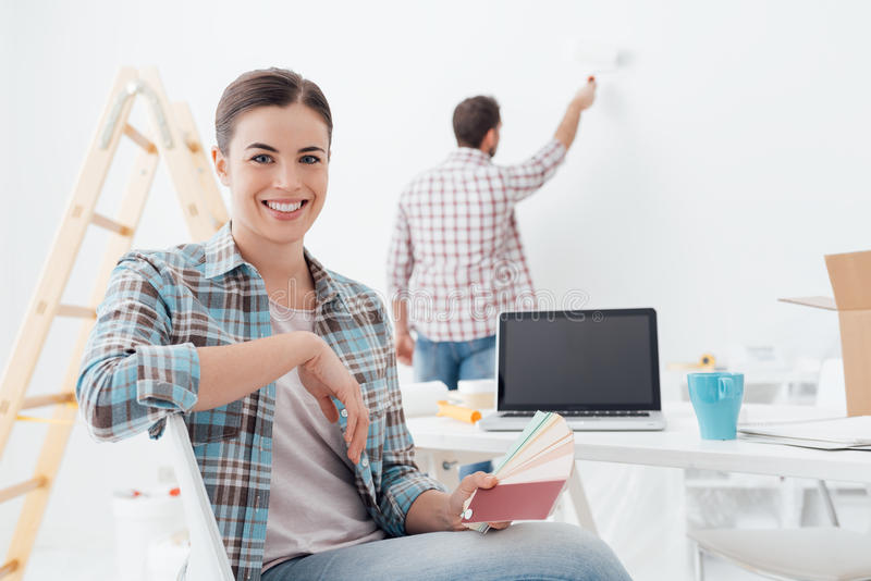Couple renovating their house. Young couple renovating their new house, the men is painting the wall with a paint roller and his girlfriend is holding color royalty free stock photo