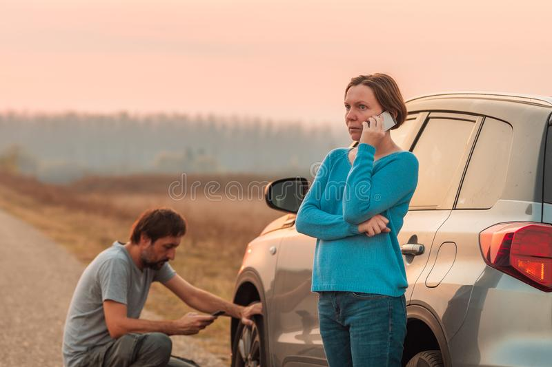 Couple repairing car flat tire on the road royalty free stock photo