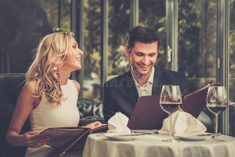 Couple in a restaurant. Cheerful couple with menu in a restaurant