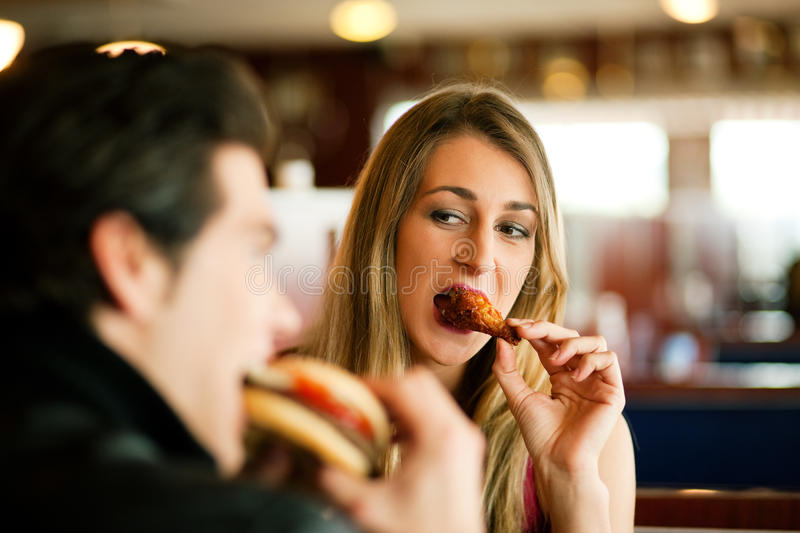 Couple in Restaurant eating fast food. Couple in a restaurant or diner eating a hamburger and chicken wings flirting the while, shot with available light, very stock photos