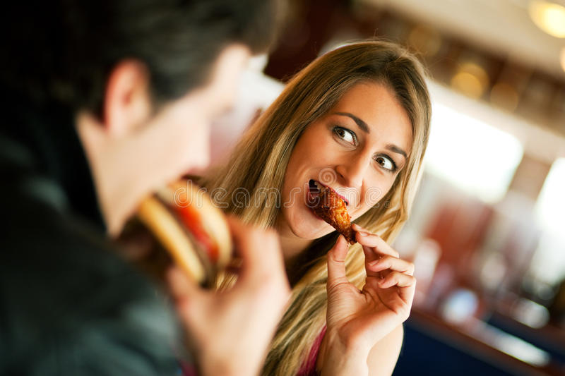 Couple in Restaurant eating fast food. Couple in a restaurant or diner eating a hamburger and chicken wings flirting the while, shot with available light, very stock image