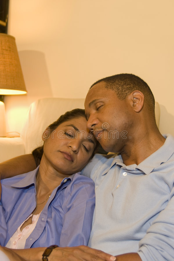 Couple Resting. An attractive and multi-ethnic couple resting with their heads together and their eyes closed. Vertically framed shot royalty free stock images