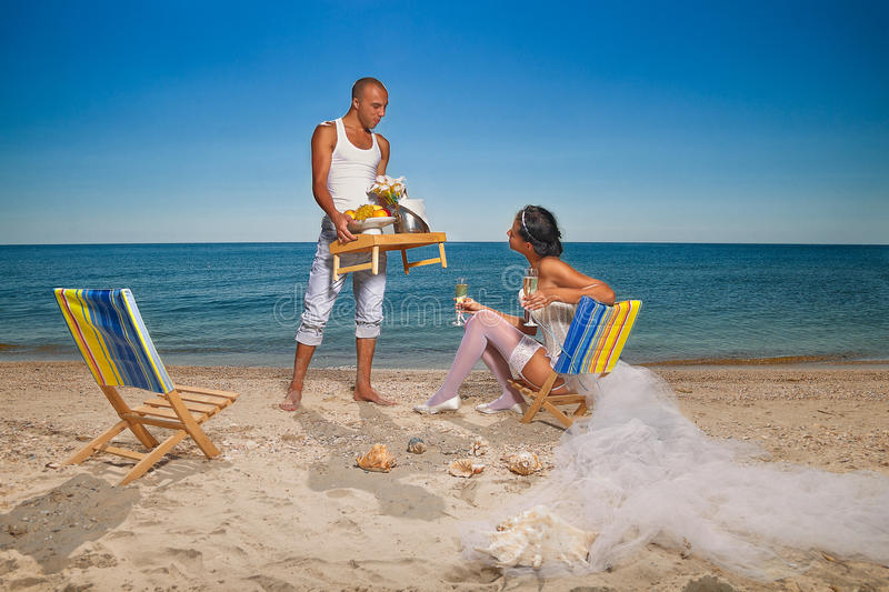 Couple resting on the beach. Romantic young couple kissing on the beach royalty free stock images