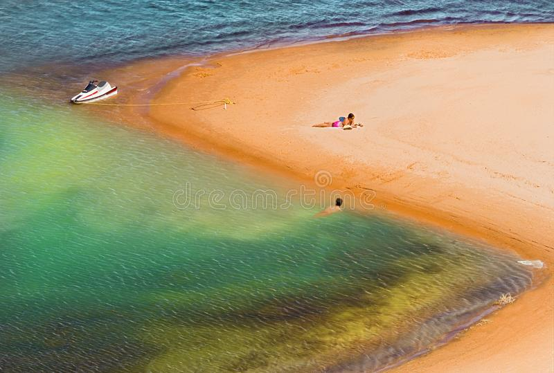 COUPLE ON GOLD SANDY BEACH RESTING WITH JET SKI IN BACKGROUND royalty free stock image