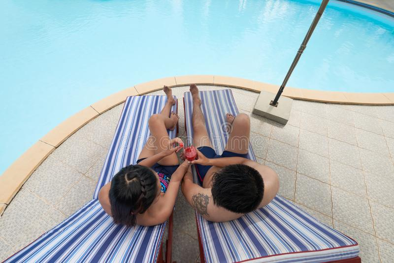 Couple resting by the pool royalty free stock images