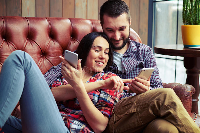 Couple resting on sofa and looking at smartphone royalty free stock images