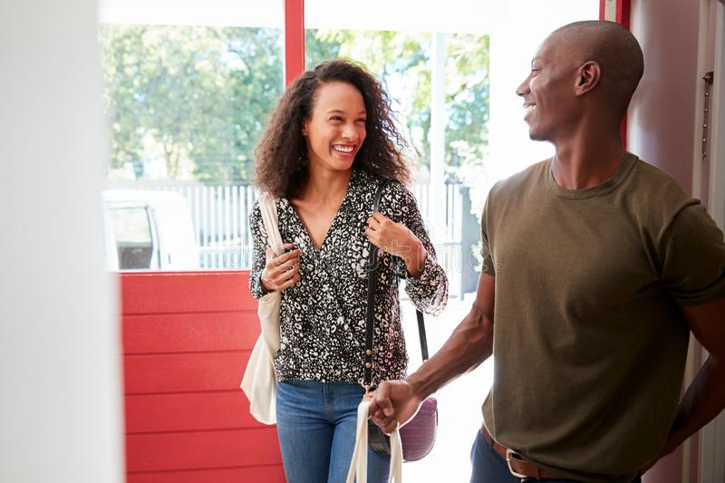 Couple Returning Home From Shopping Trip Carrying Groceries In Plastic Free Bags stock photos