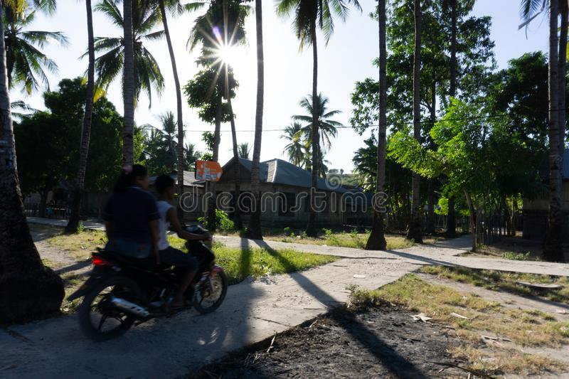 A Couple ride motor cycle on the village road stock photo