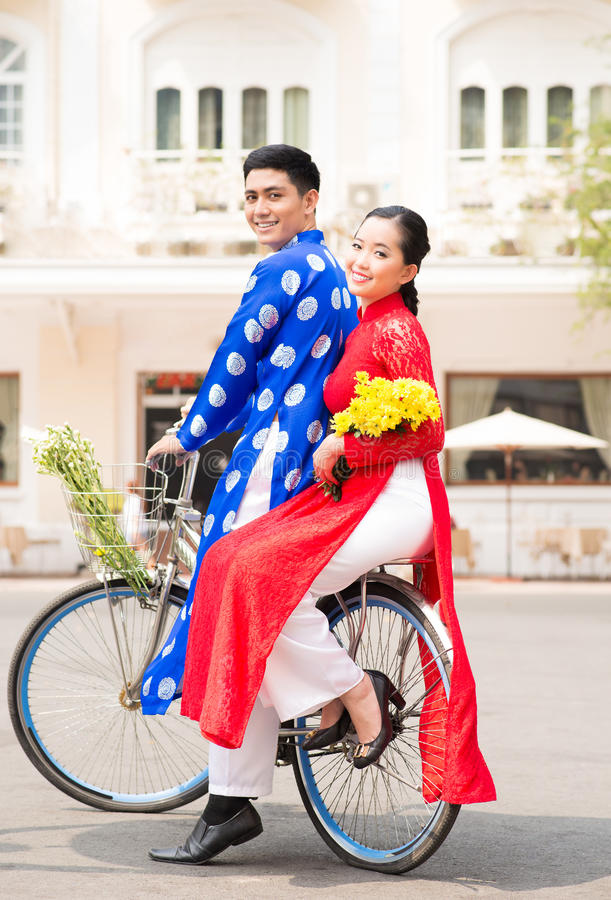 Couple riding a bicycle. Young Vietnamese couple wearing traditional clothes riding a bicycle royalty free stock photos