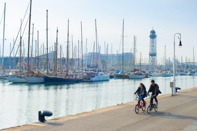 Couple riding bicycles, Barcelona marina royalty free stock image