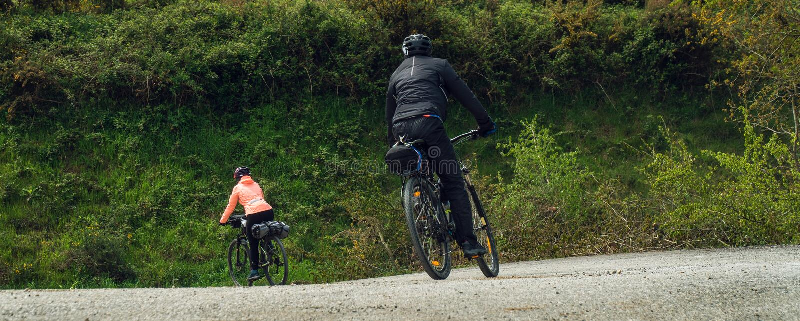 Couple riding bicycles outside. Wide view royalty free stock photography