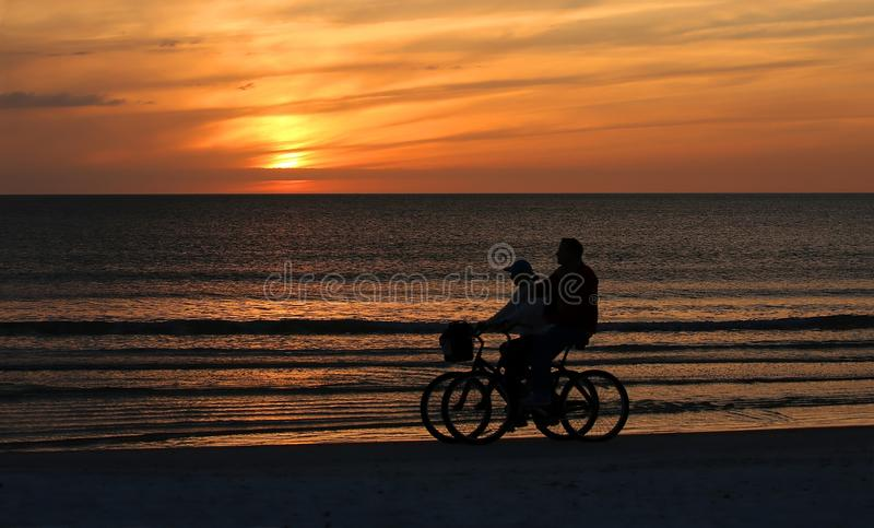 Couple riding bikes on the beach at sunset. stock images