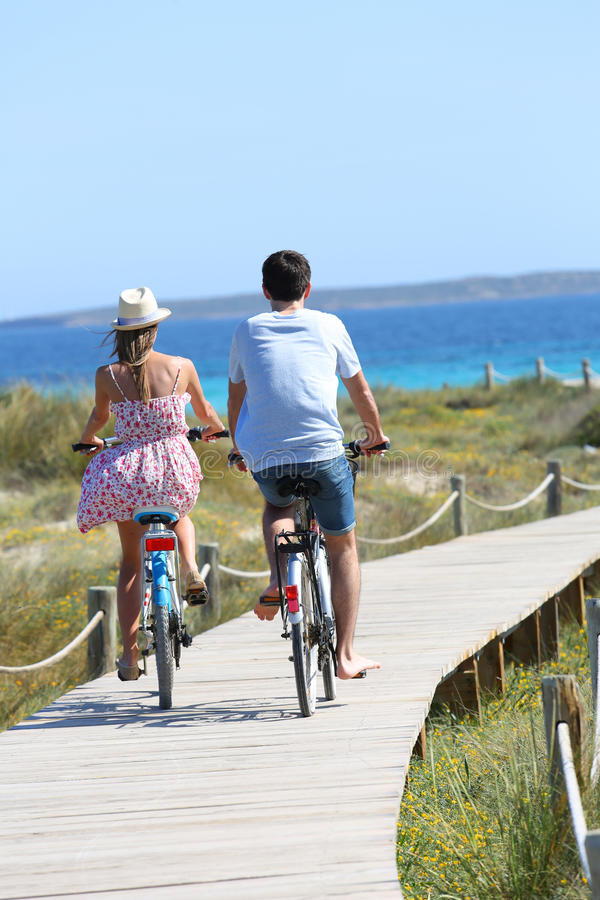 Free Couple Riding Bikes Towards The Sea Royalty Free Stock Photography - 64885577