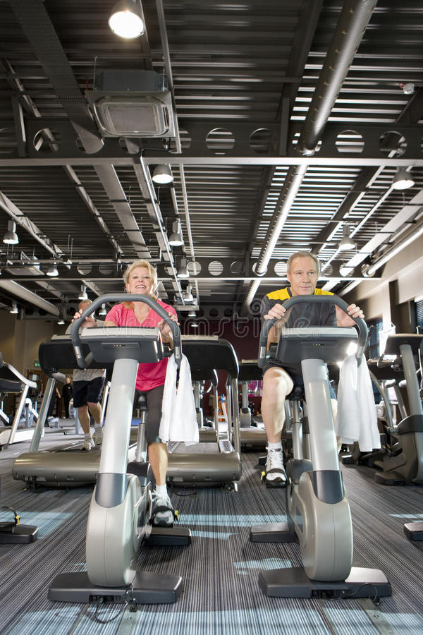 Couple riding exercise bikes in health club royalty free stock photography