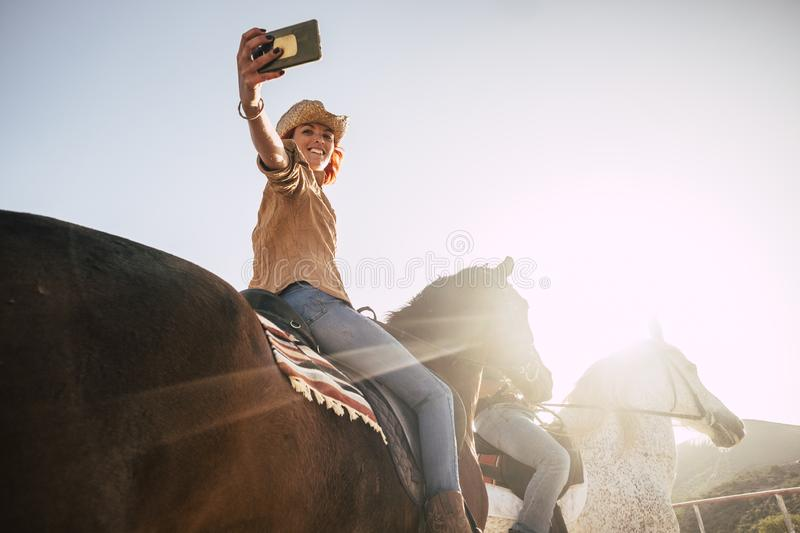 Couple riding horses take a selfie with modern technology smartphone. cowboy lifestyle and smile woman. sunset time and backlight. For outdoor leisure activity royalty free stock photo