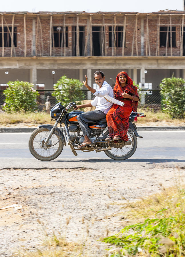 Couple riding motorbike. RAJASTHAN, INDIA - OCTOBER 18: Mother, father and small child riding on scooter through busy highway street on October 18, 2012 in stock images