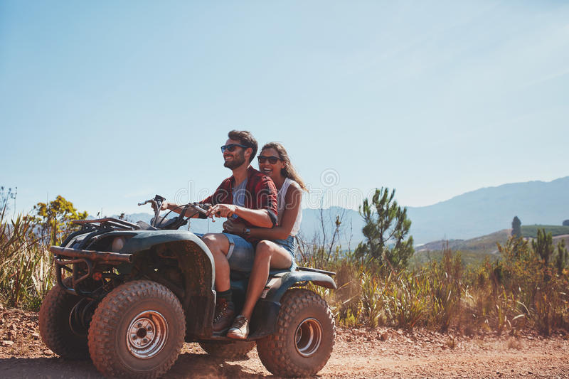 Couple riding on a quad bike royalty free stock images