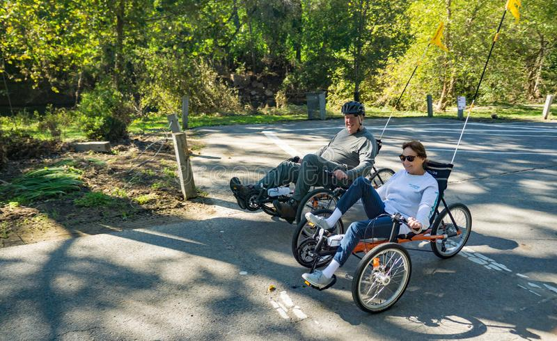 Couple Riding a Recumbent Tricycle. Roanoke, VA – OCT 19th: Couple riding a recumbent tricycle on the Roanoke River Greenway located in Wasena Park in stock photos