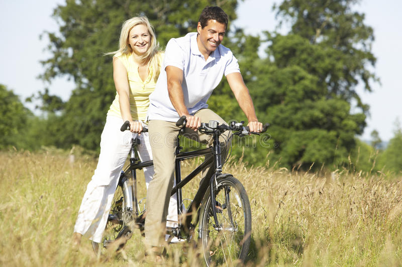 Couple riding tandem in countryside royalty free stock image