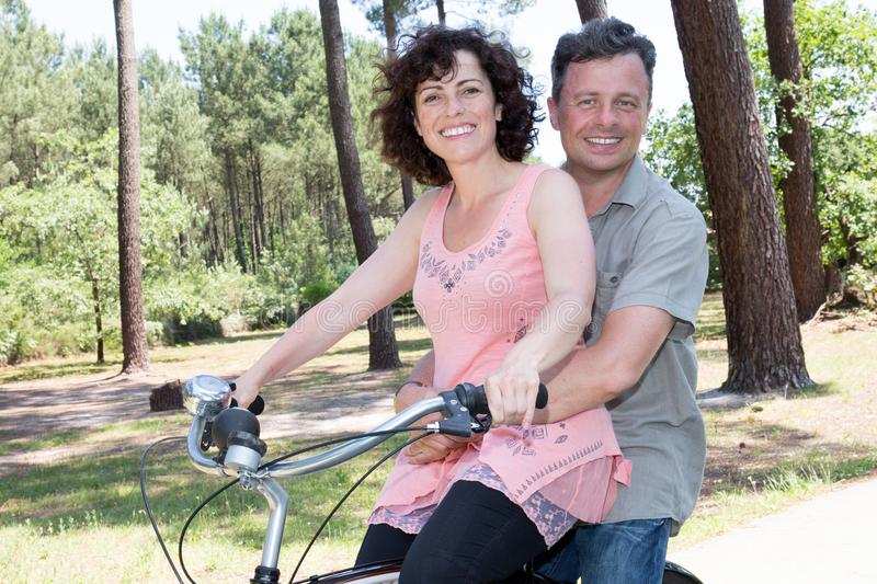 Couple riding two on bike like a tandem stock photo