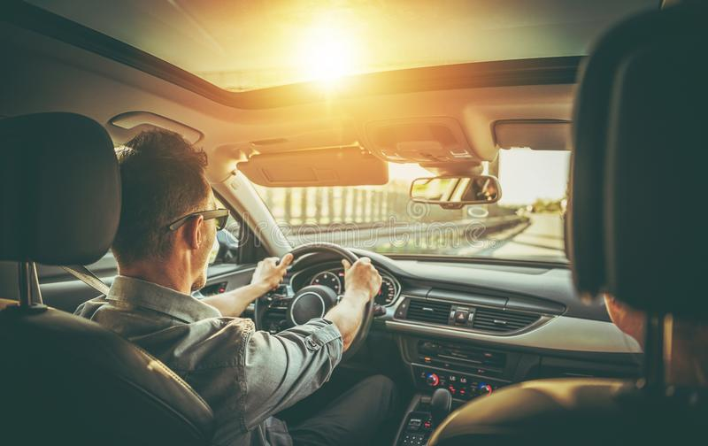 Couple on the Road Trip. Caucasian Couple on the Road Trip in the Modern Vehicle with Large Sunroof stock images