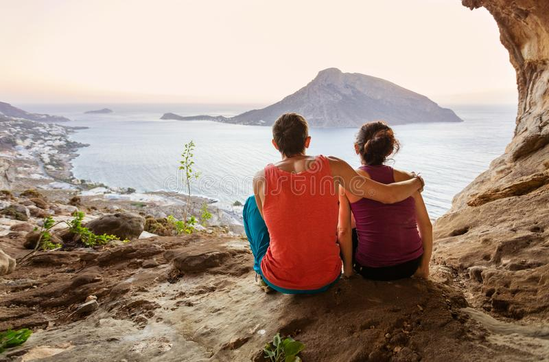 Couple of rock climbers having rest while sitting at bottom of cliff and enjoying picturesque view of Telendos Island in front stock photo