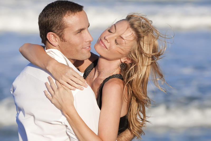 Couple In Romantic Embrace On A Beach. A young man and woman embracing as a romantic couple on a beach royalty free stock photos